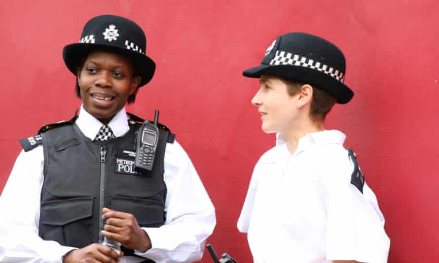 British ConstablesLondon, England - May 5th, 2008: Two female constables surveying a city market along the street. They are talking in front of a red wall. Police is needed to keep crowds in order and prevent theft.
