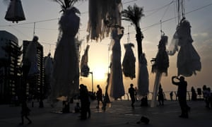 A man photographs rows of wedding dresses hanging from nooses on a Beirut beach.
