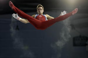 Trails of chalk follow the hands of the United States' Sam Mikulak during the artistic gymnastics horizontal bar competition at the Pan Am Games in Toronto.