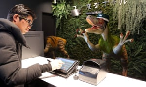 "A dinosaur robot greets a guest at a reception of the newly opened Henn na Hotel"" ("