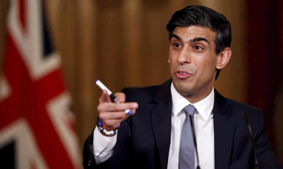 Rishi Sunak in a suit pointing at something, a union jack behind him