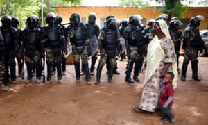 Riot police stand guard outside a polling station in Bamako.