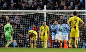 The Burton players look dejected as Manchester City's Phil Foden (No17) celebrates his goal.
