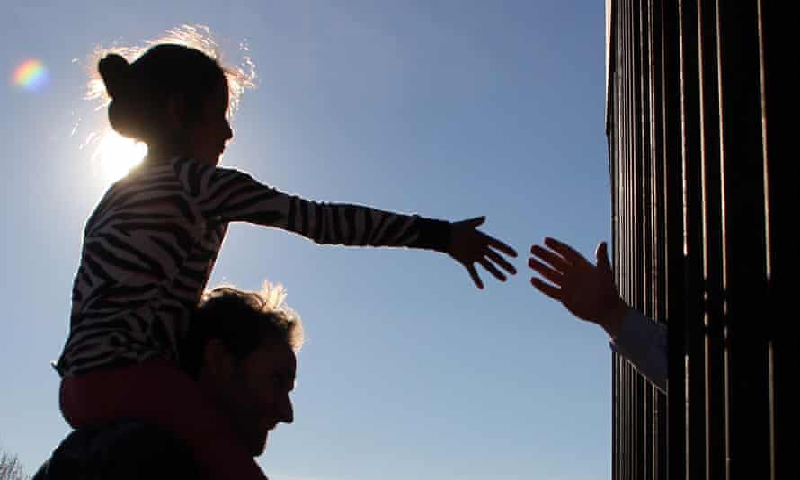 A Mexican girl touches hands with an American through the border fence