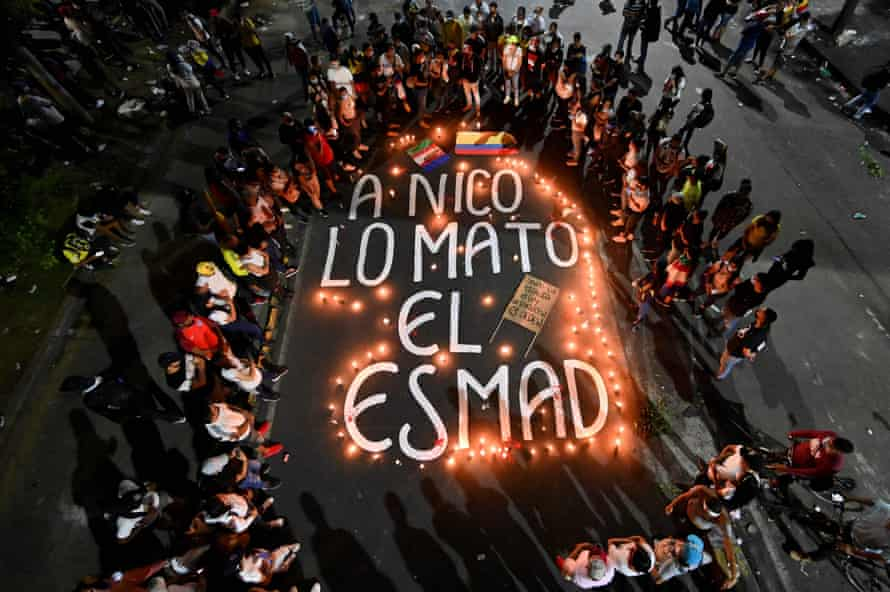 """Overhead shot of relatives and friends of Nicolás Guerrero gather around candles surrounding the words """"Nico was killed by Esmad"""