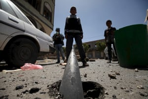 Boys stand in front of an artillery shell partially buried in the ground following an airstrike in Sana'a