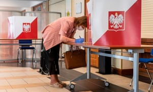 A woman wearing a protective face mask votes in Poland's Presidental election at a polling station in Warsaw.