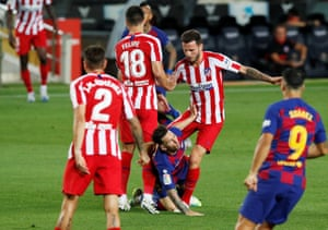 Saul Niguez takes down Barcelona's Lionel Messi.