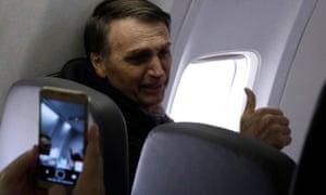 Jair Bolsonaro gestures while flying towards election engagements.