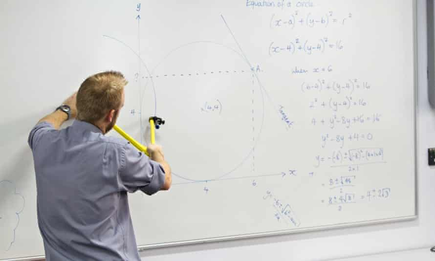A young teacher explains some workings for his maths class