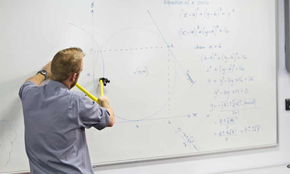 A teacher explains some workings for his maths class UK.
