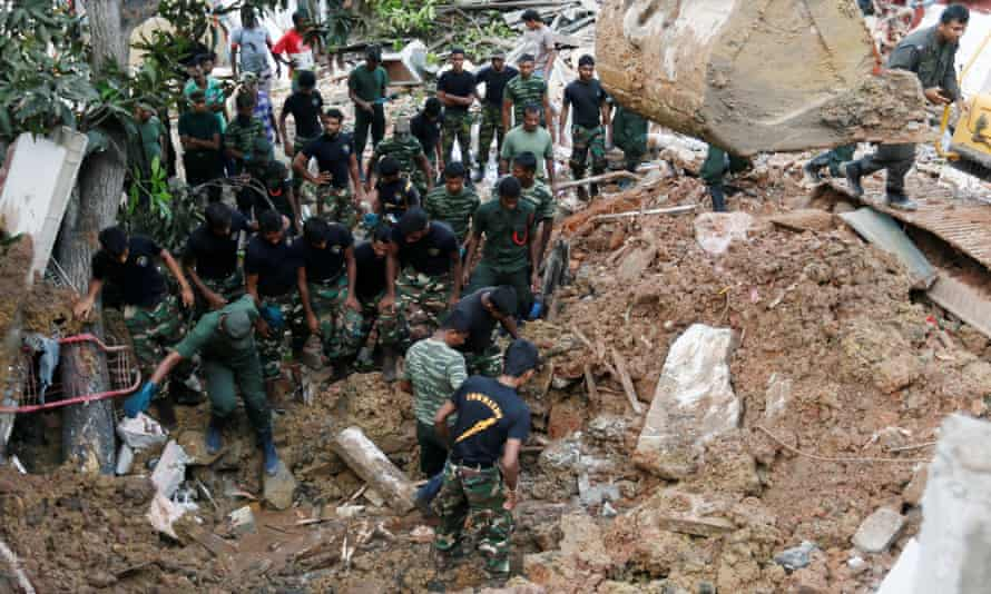 Members of the military work search for survivors after a rubbish dump in Colombo collapsed.