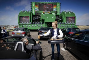 A woman gives a package to a man sitting in a car as hundred of racing fans watch the Austrian Formula One Grand Prix race at a drive-in cinema at the Zandvoort circuit, The Netherlands, on 5 July 2020, as they follow the first race of this season.