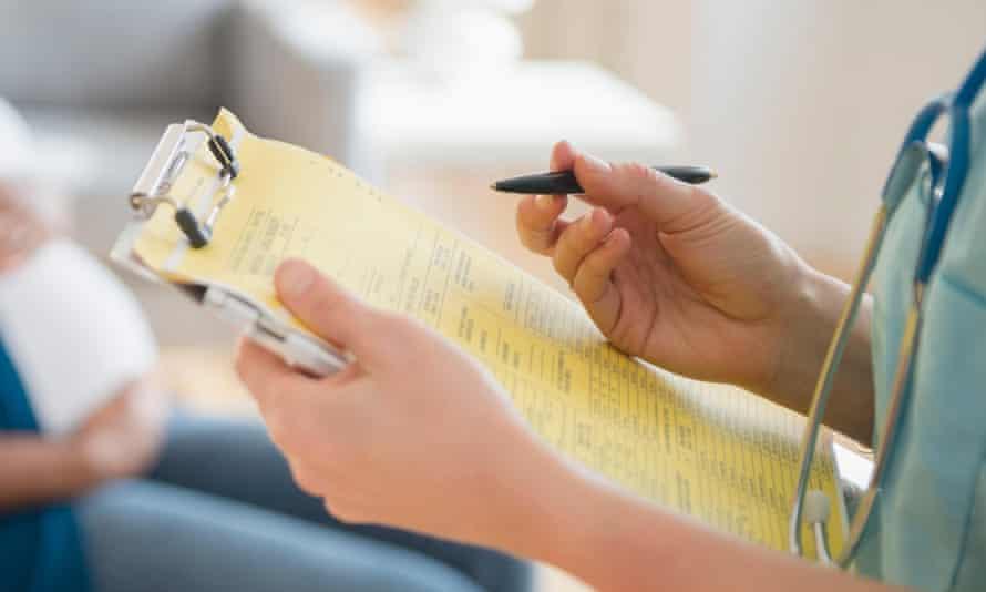 Nurse marking medical chart