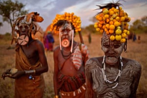 Women from the Mursi tribe pose for a photo