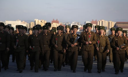 North Korean soldiers gather at Munsu Hill to lay flowers in front of statues of Kim Il Sung and Kim Jong Il.