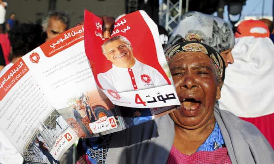 A supporter of the then jailed Tunisian presidential candidate Nabil Karoui shows his portrait during a gathering in Tunis in September.