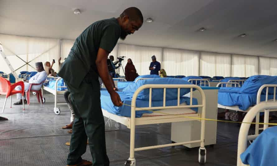 A technician measures the space between beds with a tape at a oronavirus isolation centre in Kano last month.