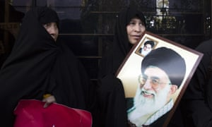 An Iranian woman holds a placard of president Rouhani during a rally in Tehran to mark the 39th anniversary of the Iran hostage crisis.