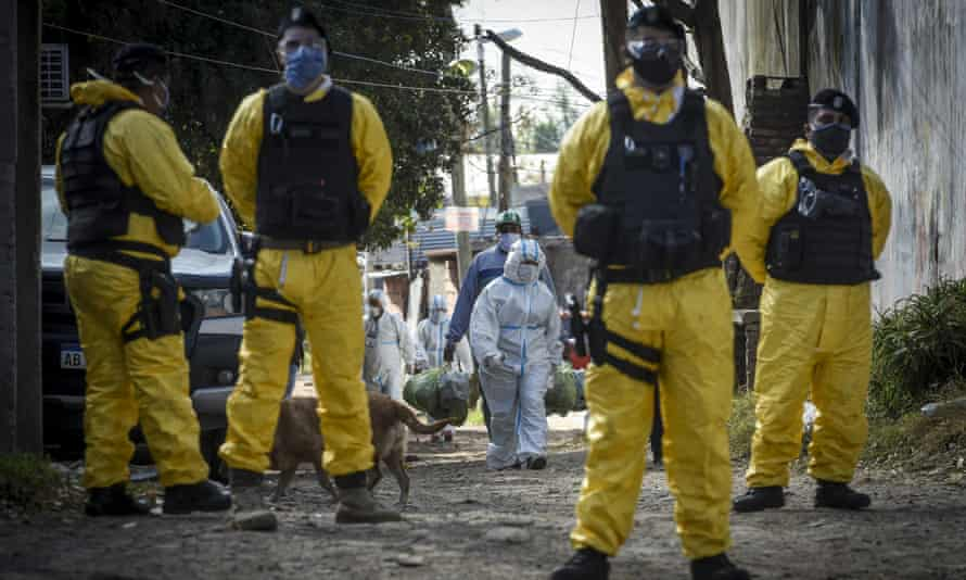Police officers wearing protective suits stand guard inside Villa Azul on Tuesday as 174 people tested positive for Covid-19.