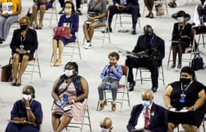 A child wearing a face mask sits among people paying their respects.