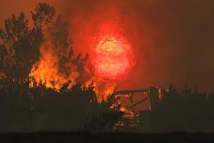 A home burns as the sun sets behind smoke and flames during the Bobcat fire in Juniper Hills, California, on Friday.