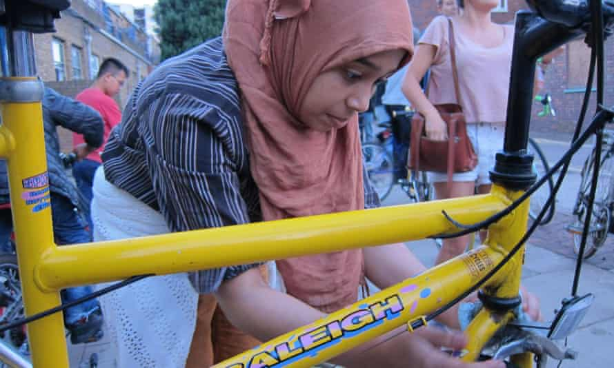 An asylum seeker works on her bike.