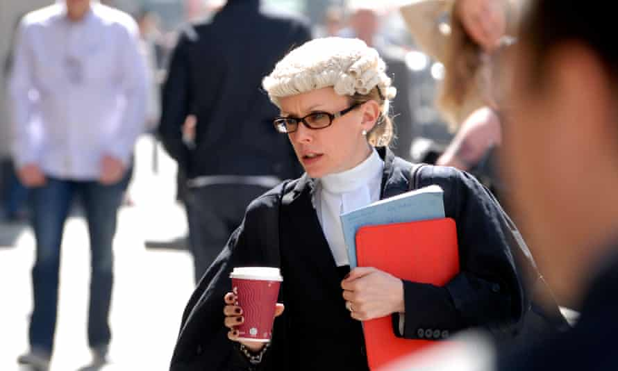 Female barrister in a hurry carrying a cup of coffee outside the Central Criminal Court, Old Bailey