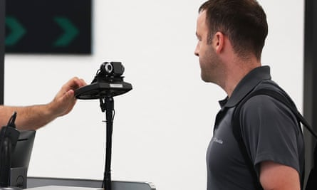 A US Customs and Border Protection officer uses facial recognition technology to screen a traveler at Miami International Airport.