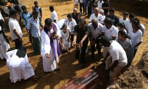 People attend a mass burial of victims at a cemetery near St Sebastian Church in Negombo on Tuesday.
