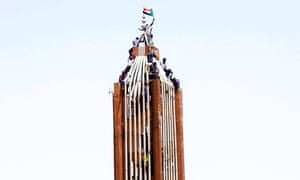 Demonstrators fly their national flag on a building near the defence ministry in Khartoum