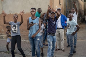 Young residents in the Alexandra township cheer at the photographer during the Covid-19 lockdown