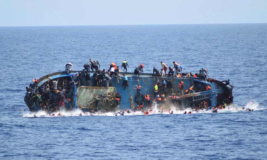 Migrants  fall into the sea from a boat that capsized last week as Italian navy ships attempted a rescue