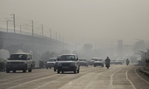 Vehicles move through morning smog on the first day of a two-week experiment to reduce the number of cars to fight pollution in Delhi.