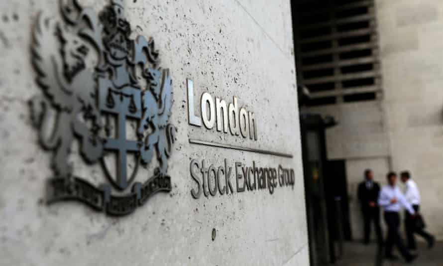 A London Stock Exchange sign with three out of focus pedestrians in the background