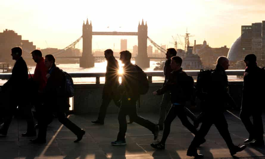 Morning commuters walk across London Bridge with Tower Bridge in the background