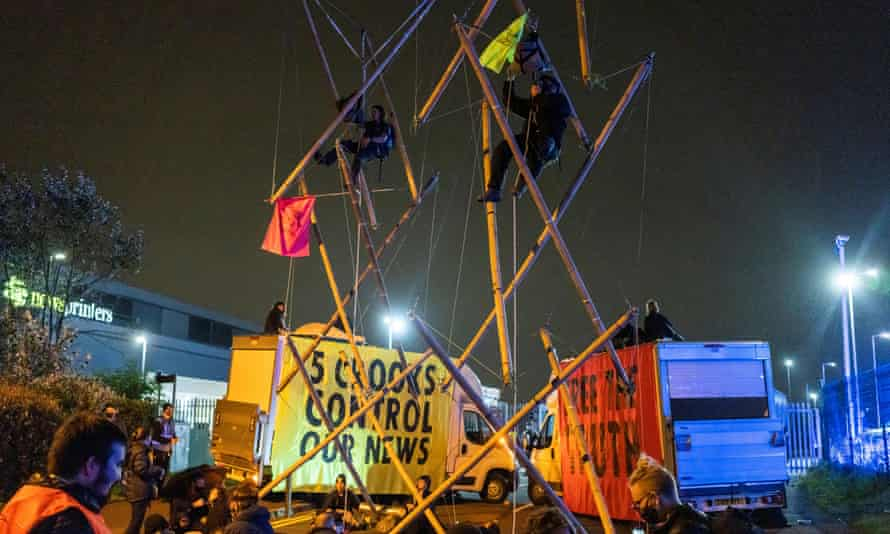 Protesters climb a bamboo scaffold between two brightly coloured vans with protest slogans on them