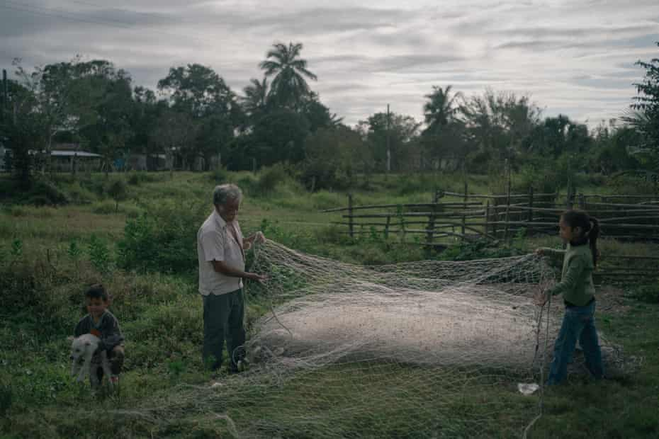 SALADERO, VERACRUZ. FEBRUARY 27: Francisco Blanco Arango untangles a fishing net with the help of his granddaughter Ada Guadalupe Blanco while Kevin Blanco Flores plays with a dog at their backyard in Saladero, Mexico.