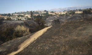Hillsides between homes in the Porter Ranch area of Los Angeles are left charred on Friday.