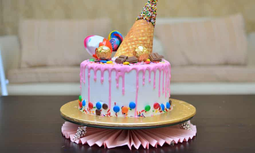 A cute pink birthday cake with an ice cream cone waffle / wafer on top with sprinkles chocolate and lollipop on top for a girl's birthday
