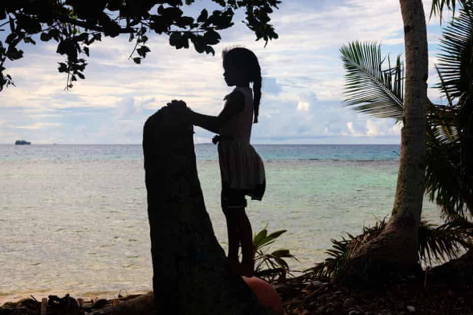 A young girl looks out onto the Funafuti lagoon
