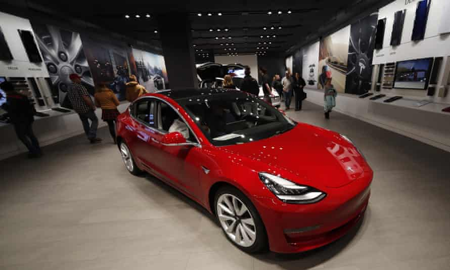 Buyers look over a Model 3 in a Tesla store in Denver.