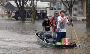 Phillip Garduno, center, Freddie Leyba, left, and his brother Christian Leyba remove personal items after using a boat to evacuate the Pecan Valley Estates on Friday in Bossier City, Louisiana.