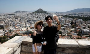 Tourists take a selfie as they visit the Acropolis hill in Athens
