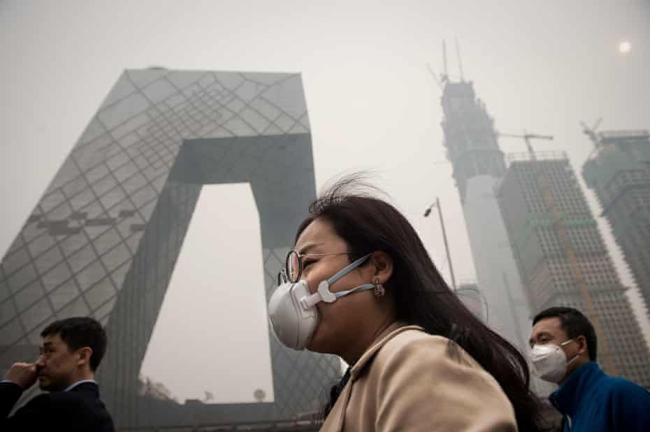 A woman wearing a protective pollution mask walks on a street in Beijing in 2017