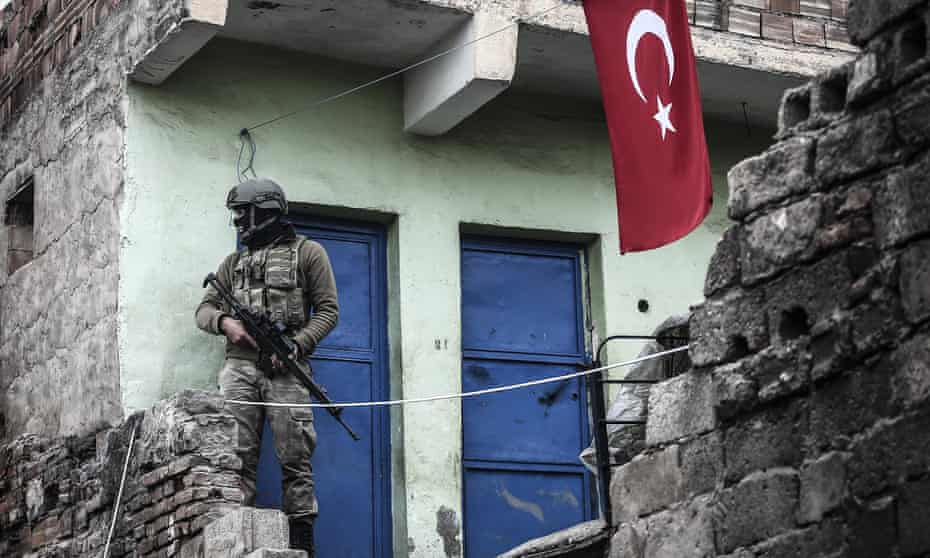 A soldier stands guard at a neighborhood as Turkish Security Forces carry out a counter - terrorism operation.