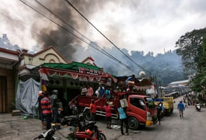 Papuan people load their belongings on a truck as smoke rises from a burning building after a violent protest in Fakfak, Wednesday, Aug. 21, 2019.
