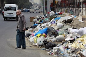 A Lebanese man covers his nose from the smell as he passes by a pile of garbage on a street in Beirut, Lebanon.