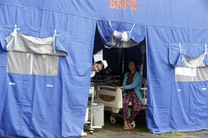 A nurse looks out of a tent where patients were evacuated from a hospital, following the earthquake.