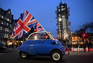 A man waves Union flags from a small car as he drives past Brexit supporters gathering in Parliament Square.